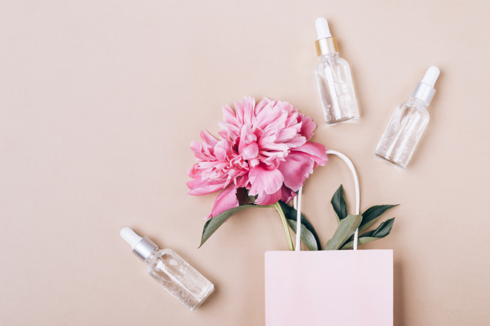 Cosmetic liquid gel products and pink peony in paper bag. Beauty skin care concept